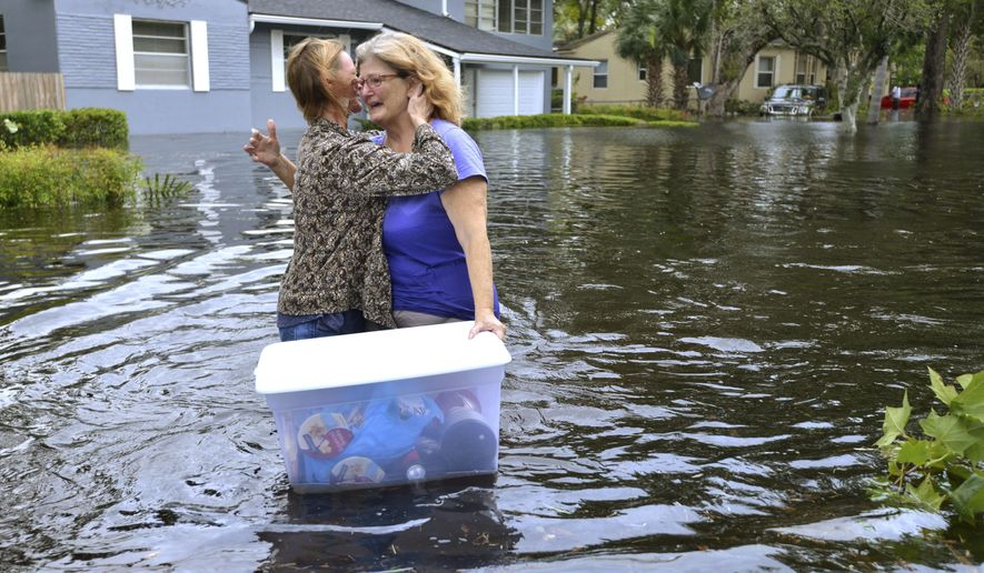 """Charlotte Glaze gives Donna Lamb a teary hug as she floats out some of her belongings in floodwaters from the Ortega River in Jacksonville, Fla., Monday, Sept. 11, 2017, after Hurricane Irma passed through the area. """"This neighborhood has not flooded in at least 51 years,"""" Lamb said. (Dede Smith/The Florida Times-Union via AP)"""