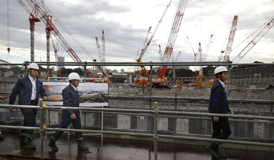 Japan's Tokyo Olympic minister Shunichi Suzuki, second left, inspects the construction of the new national stadium in Tokyo, Tuesday, Sept. 12, 2017. Tokyo's main Olympic stadium is starting to take shape as structures of what will become spectator stands are being installed after 10 months of underground foundation work. (AP Photo/Shizuo Kambayashi)