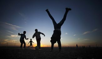FILE - In this Oct. 24, 2013, file photo, a coach's assistant does a handstand while Syrian children play soccer at the Zaatari refugee camp near the Syrian border in Jordan. Aleksander Ceferin, the head of European soccer's governing body and Jordan's Prince Ali have inaugurated a full-size soccer pitch in Jordan's largest camp for Syrian refugees. Organizers say the pitch is meant to give a sense of normalcy to 80,000 residents of Zaatari, which was set up in 2012, a year after the start of the Syria crisis. (AP Photo/Manu Brabo, File)