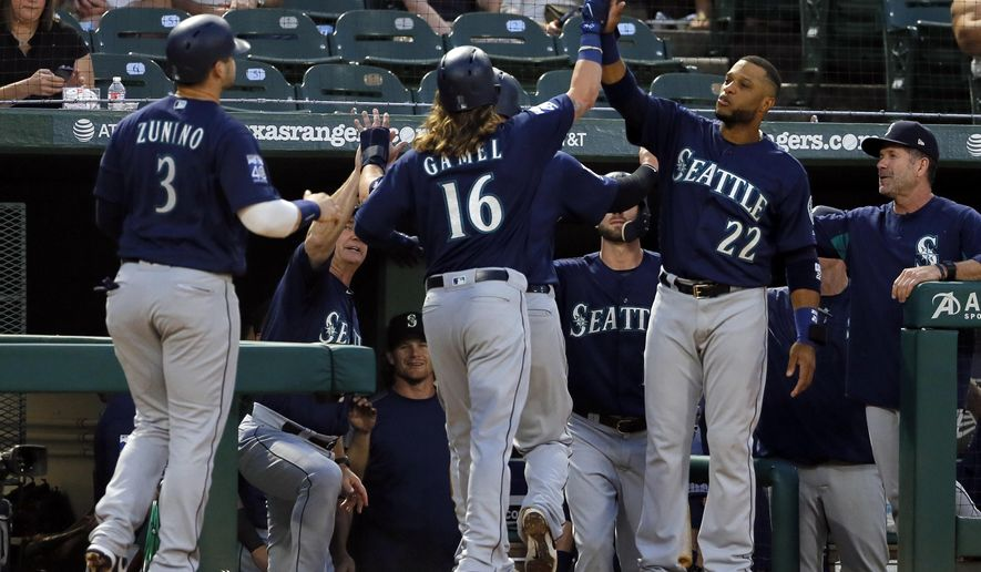 Seattle Mariners' Ben Gamel (16) is congratulated at the top of the dugout by Robinson Cano (22) after Gamel hit a three-run home run off Texas Rangers' Miguel Gonzalez that scored Mike Zunino (3) and Yonder Alonso, not seen, during the second inning of a baseball game, Tuesday, Sept. 12, 2017, in Arlington, Texas. (AP Photo/Tony Gutierrez)
