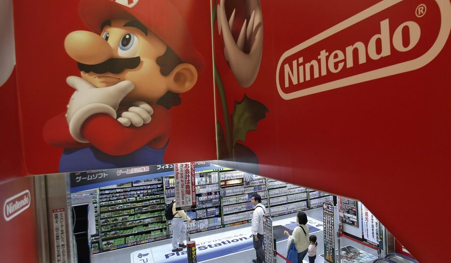FILE - In this May 7, 2014, file photo, shoppers walk under the logo of Nintendo and Super Mario characters at an electronics store in Tokyo. Nintendo announced Sept. 12, 2017, that the retro version of its iconic NES video game platform will return to store shelves next year. (AP Photo/Shizuo Kambayashi, File)