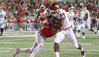 In this Saturday, Sept. 9, 2017 file photo, Oklahoma receiver Lee Morris, right, scores a touchdown as he is hit by Ohio State safety Erick Smith during the second half of an NCAA college football game, in Columbus, Ohio. Receiver Lee Morris, a sophomore walk-on, leads the team with two touchdown receptions on two catches. His 18-yard scoring grab in the third quarter against Ohio State gave the Sooners the lead for good.  (AP Photo/Jay LaPrete, File) **FIle**