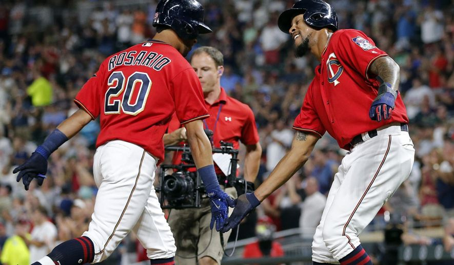 Minnesota Twins' Eddie Rosario, left, is congratulated by Byron Buxton after Rosario's two run home run off San Diego Padres relief pitcher Jose Valdez in the fourth inning of a baseball game Tuesday, Sept. 12, 2017, in Minneapolis. (AP Photo/Jim Mone)
