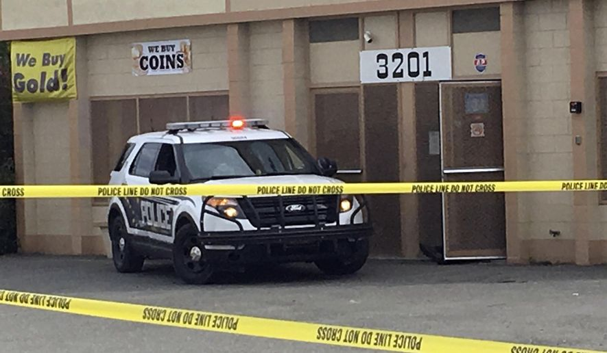 The foot of a shooting victim can be seen sticking out of the doorway of a precious metal shop in Anchorage, Alaska, Tuesday, Sept. 12, 2017. Police say three people are dead following the shooting. Anchorage police say the shootings occurred Tuesday at The Bullion Brothers, a shop with displays of gold and silver coins. (AP Photo/Mark Thiessen)