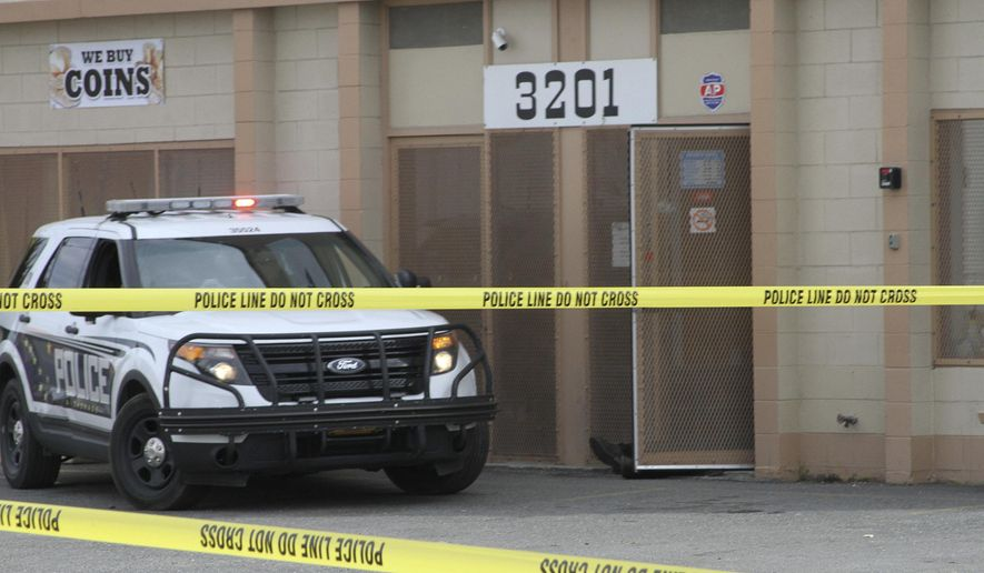 The legs of one shooting victim are shown sticking out from a precious-metals store in Anchorage, Alaska, on Tuesday, Sept. 12, 2017. Three people were killed, and police say they have a suspect in custody. (AP Photo/Mark Thiessen)
