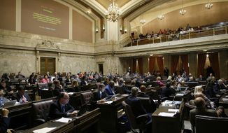 FILE - In this June 30, 2017, file photo, representatives work on the House floor during discussion of a bill to fully fund education in Washington state at the Capitol in Olympia, Wash. A coalition of news organizations led by The Associated Press is suing the Washington Legislature over its assertion that state lawmakers aren't required to turn over daily schedules, text messages, emails and other materials related to their work. (AP Photo/Ted S. Warren, File)