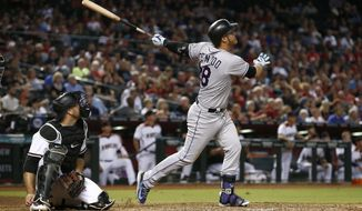 Colorado Rockies' Nolan Arenado, right, watches the flight of his three-run home run as Arizona Diamondbacks' Chris Iannetta, left, looks on during the eighth inning of a baseball game Monday, Sept. 11, 2017, in Phoenix. (AP Photo/Ross D. Franklin)