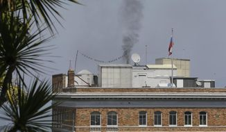 In this photo taken Sept. 1, 2017, black smoke rises from the roof at the Consulate-General of Russia in San Francisco. San Francisco's air board is citing Russian diplomats over the mysterious black smoke that wafted out of their consulate here in the hours after the United States ordered it shut down. (AP Photo/Eric Risberg)