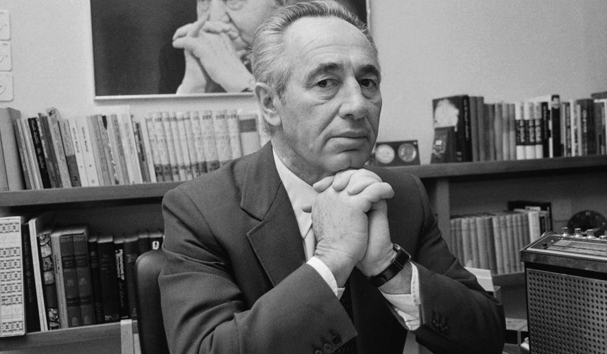 FILE - In this June 1981 file photo, Shimon Peres, then the leader of the Israeli opposition, poses in front of a picture of David Ben-Gurion, at his office in Tel Aviv, Israel. Peres had an unprecedented seven decades of public service packed with historic triumphs and painful setbacks. In a memoir  completed shortly before his death in 2016, that came out Tuesday, Sept. 12, 2017, the former Israeli president and prime minister offers his trademark optimistic blueprint for future leadership but also a rare glimpse into key chapters of his extraordinary life. (AP Photo, File)