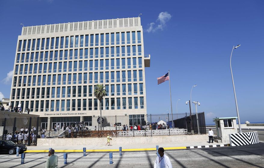 In this photo taken Aug. 14, 2015, a U.S. flag flies at the U.S. embassy in Havana, Cuba. Two more American diplomats who served in Cuba are affected by health attacks in Cuba, raising the total to 21. (AP Photo/Desmond Boylan)