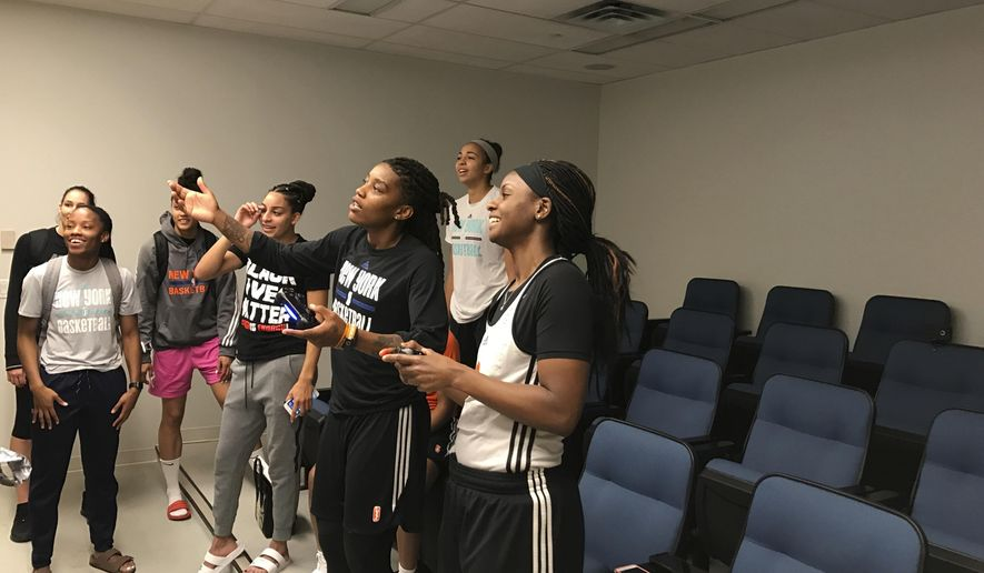 Sugar Rodgers, far right, holds the controller alongside Shavonte Zellous, center, while they play NBA Live while Tina Charles and other New York Liberty teammates look on Saturday, Sept. 9, 2017 at the team's practice facility in Tarrytown, N.Y. (AP Photo/Doug Feinberg)