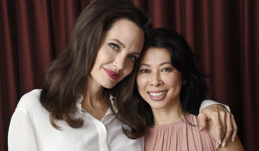 """In this Sept. 11, 2017 photo, Angelina Jolie, left, director/co-writer of the film """"First They Killed My Father: A Daughter of Cambodia Remembers,"""" and co-writer/human rights activist Loung Ung pose for a portrait during the Toronto International Film Festival in Toronto. (Photo by Chris Pizzello/Invision/AP)"""