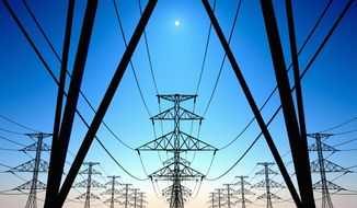 Electricity pylons and lines on a clear blue sky.