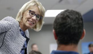 """Education Secretary Betsy DeVos talks to a student in a coding class in Omaha, Neb., Wednesday, Sept. 13, 2017, during a visit to the Midland University-Omaha Campus as part of her 2017 """"Rethink School"""" tour, in which she plans to visit schools in Wyoming, Colorado, Nebraska and Kansas. (AP Photo/Nati Harnik)"""
