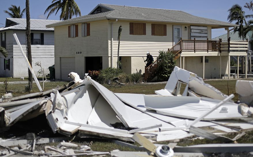 A member of the Arizona Task Force 1 search and rescue team knocks on doors while checking on homes and their owners after Hurricane Irma in Goodland, Fla., Tuesday, Sept. 12, 2017. (AP Photo/David Goldman)