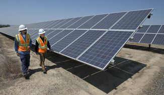 In this Thursday, Aug. 17, 2017, file photo, solar tech Joshua Valdez, left, and senior plant manager Tim Wisdom walk past solar panels at a Pacific Gas and Electric Solar Plant, in Dixon, Calif. Higher energy costs led to prices at the wholesale level rising in August 2017 at the fastest pace in four months, according to information released Wednesday, Sept. 13, 2017, by the Labor Department. (AP Photo/Rich Pedroncelli, File)
