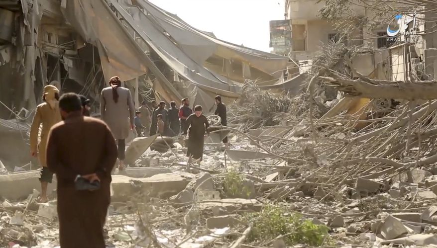 This undated file frame grab from video posted online Monday, May 29, 2017 by the Aamaq News Agency, a media arm of the Islamic State group, shows people inspecting damage from airstrikes and artillery shelling in the northern city of Raqqa, Syria. (Aamaq News Agency via AP, File) ** FILE **