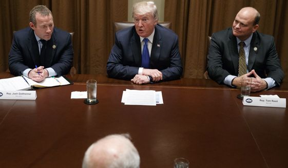 Rep. Josh Gottheimer, D-N.J., left, and Rep. Tom Reed, R-N.Y., right, listen as President Donald Trump speaks during a meeting with a bipartisan group of lawmakers in the Cabinet Room of the White House, Wednesday, Sept. 13, 2017, in Washington. (AP Photo/Evan Vucci)