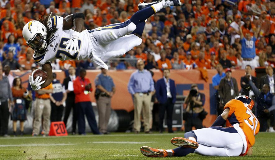 Los Angeles Chargers running back Melvin Gordon (28) dives over Denver Broncos strong safety Justin Simmons (31) for a touchdown during the first half of an NFL football game, Monday, Sept. 11, 2017, in Denver. (AP Photo/Jack Dempsey)