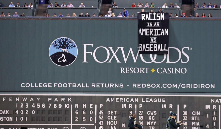 A banner is unfurled over the left field wall during the fourth inning of a baseball game between the Boston Red Sox and the Oakland Athletics at Fenway Park in Boston, Wednesday, Sept. 13, 2017. (AP Photo/Charles Krupa)