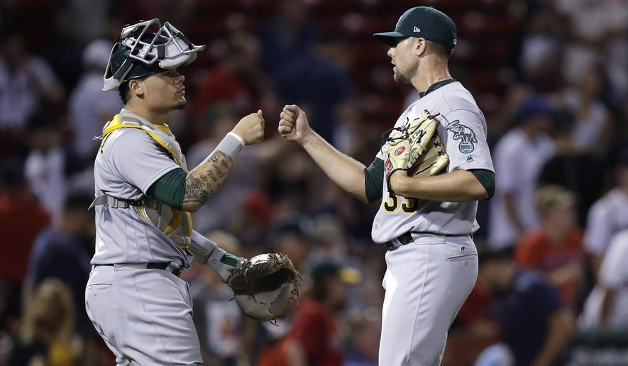 Oakland Athletics relief pitcher Blake Treinen, right, celebrates with catcher Bruce Maxwell after the A's defeatedthe Boston Red Sox 7-3 in a baseball game at Fenway Park in Boston, Wednesday, Sept. 13, 2017. (AP Photo/Charles Krupa)