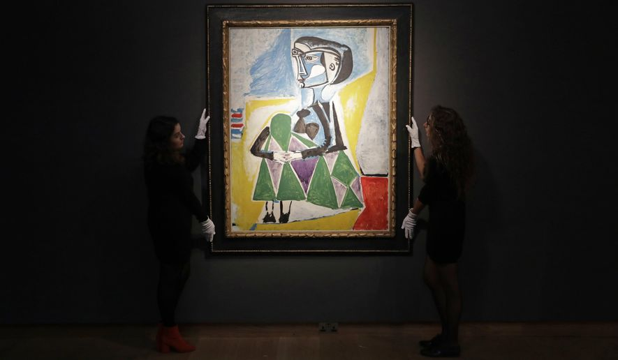 """Christie's auction house staff pose for photographs with the 1954 Pablo Picasso painting """"Femme accroupie (Jacqueline)"""", a portrait of Jaqueline Roque, Picasso's final great muse and eventually his second wife, at their premises in London, Wednesday, Sept. 13, 2017. The painting is estimated to fetch between $20 and $30 million (16.7 and 25 million euro) in an Evening Sale of Impressionist and Modern Art on November 13 in New York. (AP Photo/Matt Dunham)"""