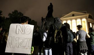 "A group of protesters stand in front of the Rotunda at the University of Virginia for the one month anniversary of the ""Unite the Right"" rally in Charlottesville, Va., Tuesday, Sept. 12, 2017. The group circled around the statue of Thomas Jefferson before covering it with black tarp and listing demands for the university. (Zack Wajsgras/The Daily Progress via AP)"