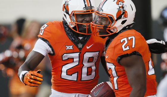 FILE - In this Aug. 31, 2017, file photo, Oklahoma State running back J.D. King (27) celebrates a touchdown with teammate James Washington (28) during the first half of an NCAA college football game against Tulsa in Stillwater, Okla., Thursday, Aug. 31, 2017. Oklahoma State plays at Pittsburgh this week. (AP Photo/Sue Ogrocki, File)