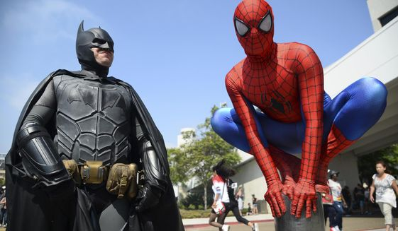 "FILE - In this July 23, 2016 file photo, Dorian Black, left, dressed as Batman and Kyle Blankenfield, dressed as Spider-Man appear outside during Comic-Con International in San Diego. A court battle between two rival pop-culture conventions in California and Utah is marching on with a judge's refusal to toss out the case over rights to the phrase ""comic con."" U.S. District Judge Anthony Battaglia made a split decision Tuesday, Sept. 12, 2017, in the case that started when the well-known San Diego Comic-Con sued upstart rivals in Salt Lake City for trademark violation.  (Photo by Al Powers/Invision/AP, File)"