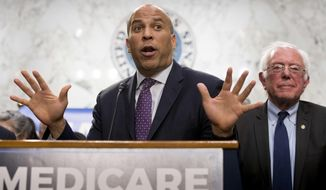 Sen. Cory Booker, D-N.J., left, accompanied by Sen. Bernie Sanders, I-Vt., right, speaks during a news conference on Capitol Hill in Washington, Wednesday, Sept. 13, 2017, to unveil their Medicare for All legislation to reform health care. (AP Photo/Andrew Harnik) **FILE**