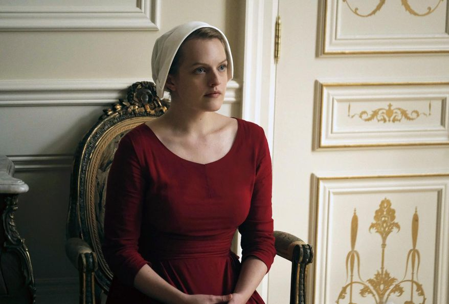 """This image released by Hulu shows Elisabeth Moss as Offred in a scene from, """"The Handmaid's Tale."""" The program is nominated for an Emmy Award for outstanding drama series.  The Emmy Awards ceremony, will air on Sept. 17. (George Kraychyk/Hulu via AP)"""