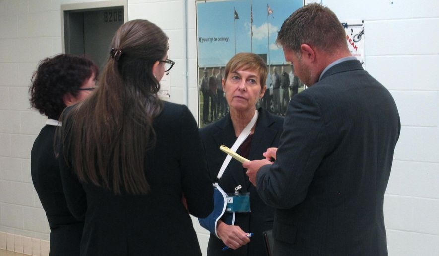 "Federal public defender Carol Wright, second from right, briefs other attorneys and members of a team representing condemned inmate Gary Otte following Otte's execution on Wednesday, Sept. 13, 2017, in Lucasville, Ohio. Wright, who witnessed the execution, believes Otte's rising and falling stomach indicated he was suffering from a phenomenon known as ""air hunger"" and she tried unsuccessfully to leave the witness room and alert a federal judge. She said the judge declined to stop the procedure, though it was likely too late at that point. (AP Photo/Andrew Welsh-Huggins)"