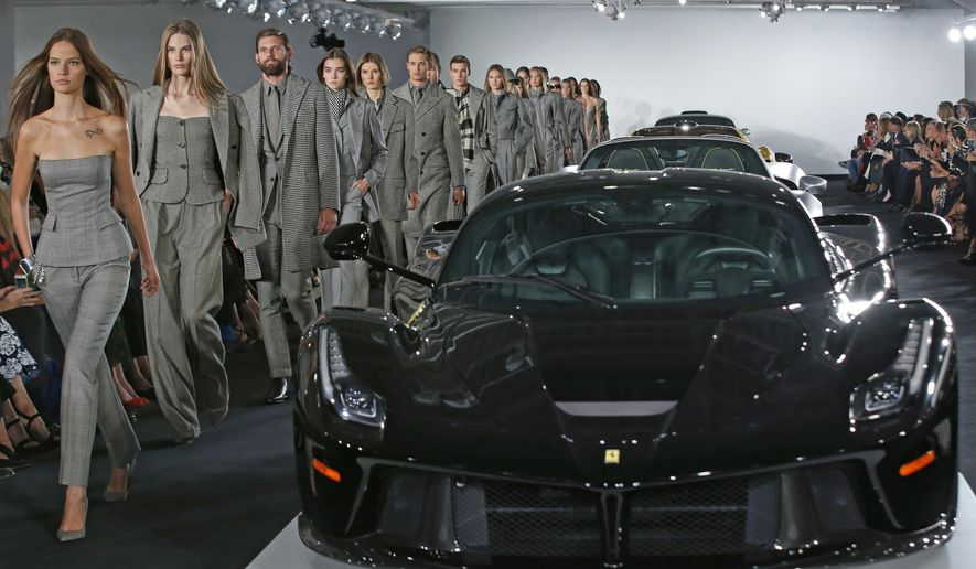 Models walk the runway beside Ralph Lauren's car collection in The Garage at the Ralph Lauren fashion show during Fashion Week, Tuesday, Sept. 12, 2017, in Bedford, N.Y. (AP Photo/Kathy Willens)