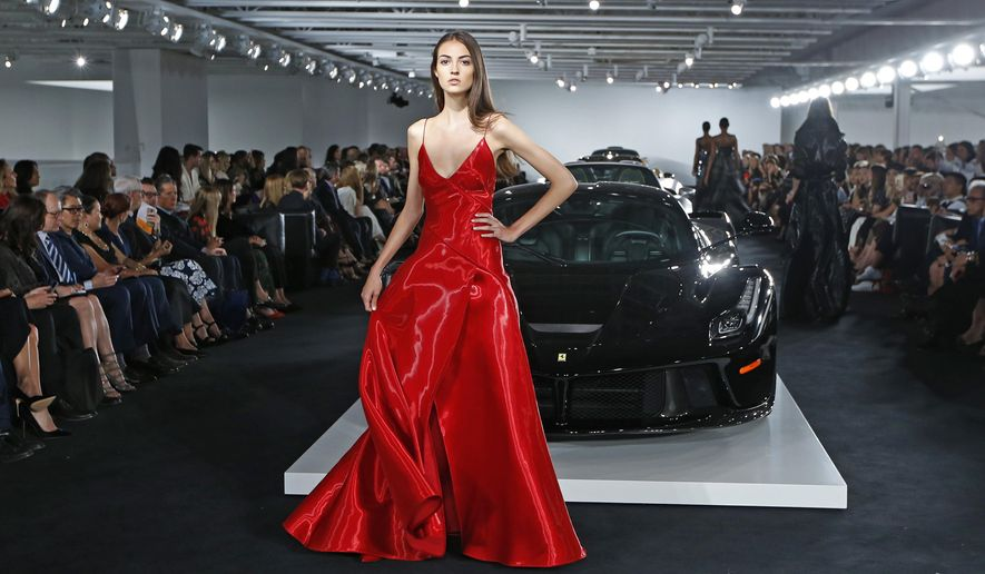 A model pauses in front of Ralph Lauren's car collection in The Garage at the Ralph Lauren fashion show during Fashion Week, Tuesday, Sept. 12, 2017, in Bedford, N.Y. (AP Photo/Kathy Willens)