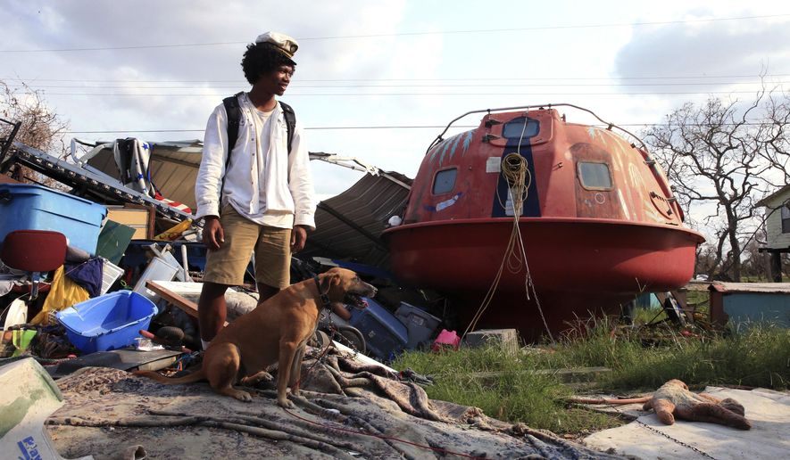 "In a Sept. 6, 2017 photo, Davonn Phothiboupha stands near a ""hurricane pod"" that she stayed in, bought by Linda Caster, a resident of Holiday Beach in Aransas County, Texas, as Hurricane Harvey made landfall. Three people and two dogs stayed inside the pod when Hurricane Harvey made its second landfall with 130 mph winds in Aransas County on Aug. 26. and Phothiboupha said it saved their lives.  (Rachel Denny Clow/Corpus Caller-Times, via AP)"