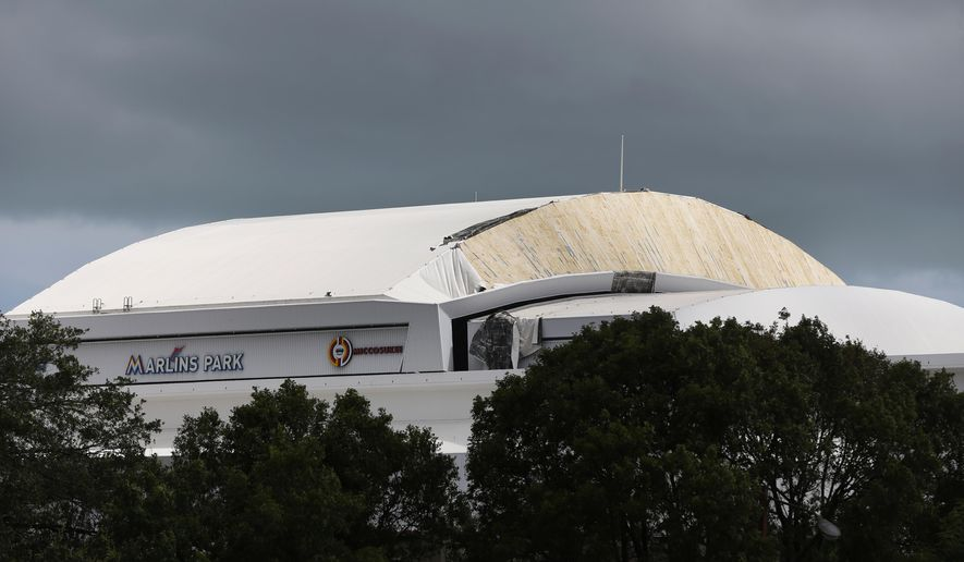 Part of the Retractible roof's membrane at Miami's Marlins Park stadium, where the Miami Marlins play baseball, is seen peeled off Monday, Sept. 11, 2017, in the wake of Hurricane Irma. (AP Photo/Wilfredo Lee)