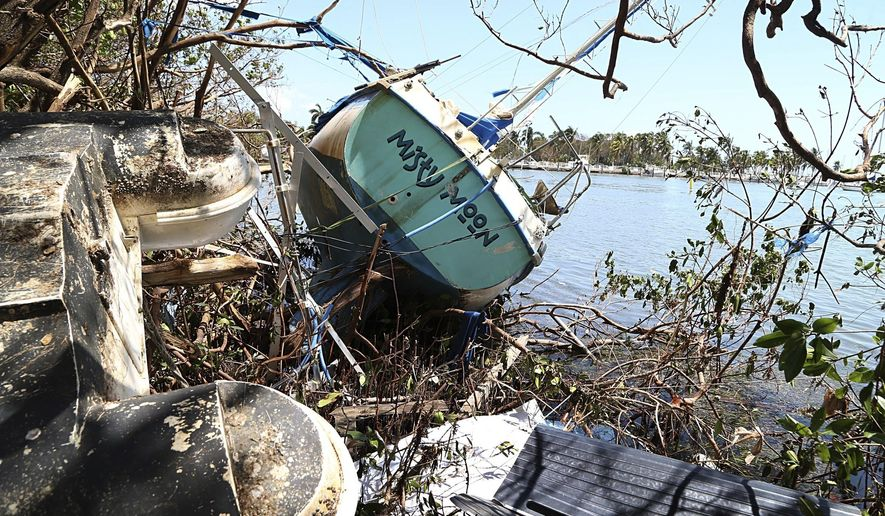 A damaged sail boat washed ashore is seen at Grove Key Marina after Hurricane Irma, Tuesday, Sept. 12, 2017, in Miami. (Pedro Portal/Miami Herald via AP)