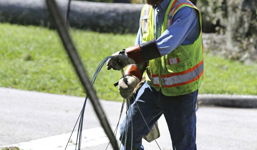 A Duke Energy contractor coils downed power lines along Dommerich Drive during the first stage of assessment and restoration in the aftermath of Hurricane Irma, Wednesday, Sept. 13, 2017, in Maitand, Fla. The storm dragged down power lines and blew out transformers knocking out power to millions across Florida. (Joe Burbank/Orlando Sentinel via AP)