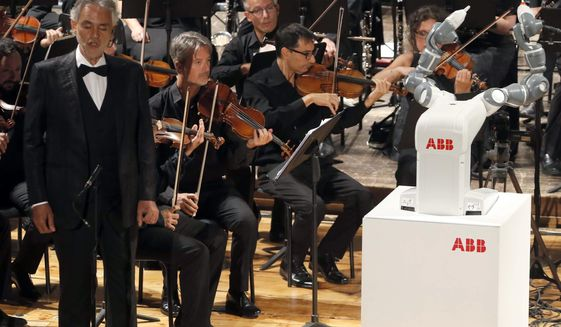 "Italian tenor Andrea Bocelli, left, performs Giuseppe Verdi's opera ""La Donna e' Mobile"", on stage next to the robot YuMi conducting the Lucca Philharmonic Orchestra, at the Verdi Theater, in Pisa, Italy, Tuesday, Sept. 12, 2017. A world famous tenor, a celebrated orchestra and a robot conductor were the highlight of Pisa's inaugural International Robotics Festival which runs from Sept. 7 to Sept. 13. (International Robotics Festival Pisa via AP)"