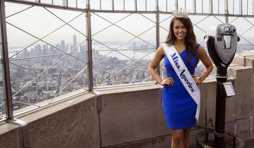 Newly-crowned Miss America 2018 Cara Mund poses for photographers on the 86th Floor Observation Deck of the Empire State Building, Tuesday, Sept. 12, 2017, in New York. The 23-year-old from North Dakota won the crown Sunday night after saying in an onstage interview that President Donald Trump was wrong to pull the United States out of the Paris climate accord (AP Photo/Mary Altaffer)