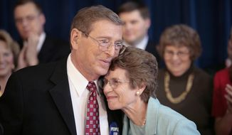 FILE - In this Thursday, Oct. 4, 2007, file photo, Sen. Pete Domenici, R-N.M., embraces his wife Nancy, right, as he finishes a news conference, in Albuquerque, N.M. Domenici, who became a power broker in the Senate for his work on the federal budget and energy policy, has died. Domenici was 85. The law firm of Pete Domenici Jr., the senator's son, confirms that the former lawmaker died Wednesday, Sept. 13, 2017, in Albuquerque but did not provide any details. (AP Photo/Toby Jorrin, File)