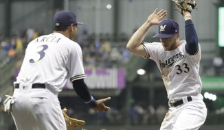 Milwaukee Brewers' Brett Phillips (33) is congratulated by Orlando Arcia after throwing out Pittsburgh Pirates' David Freese at home during the fourth inning of a baseball game Wednesday, Sept. 13, 2017, in Milwaukee. (AP Photo/Morry Gash)