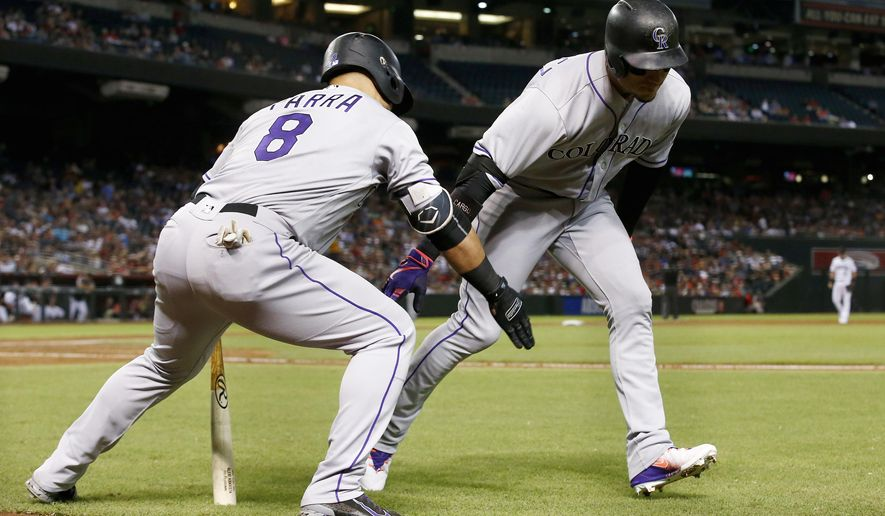 Colorado Rockies' Carlos Gonzalez, right, celebrates his two-run home run against the Arizona Diamondbacks with Gerardo Parra (8) during the third inning of a baseball game Tuesday, Sept. 12, 2017, in Phoenix. (AP Photo/Ross D. Franklin)
