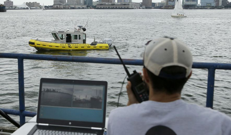 In this Aug. 15, 2017 photo, computer scientist Mohamed Saad Ibn Seddik, of Sea Machines Robotics, uses a laptop to guide a boat outfitted with sensors and self-navigating software and capable of autonomous navigation in Boston Harbor. The boat still needs human oversight, but some of the world's biggest maritime firms have committed to designing ships that won't need any captains or crews - at least not on board. (AP Photo/Steven Senne)