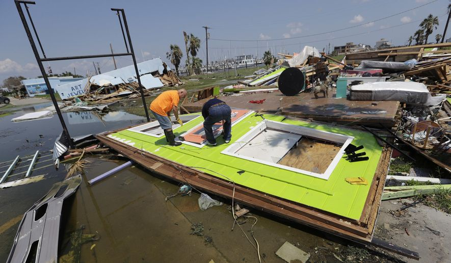 FILE - In this Saturday, Sept. 2, 2017, file photo, people work to remove a door from what had been an interior wall of a business, in Rockport, Texas, in the aftermath of Harvey. Small businesses with customers or suppliers along the Gulf Coast and in Florida are feeling the financial impact from Hurricanes Harvey and Irma. Sales have dropped off as people and businesses prepared for the hurricanes, and are still down as everyone assesses and deals with the devastation left by the storms. Many companies located far away have to strategize to boost their sales and in some cases, find alternative vendors. (AP Photo/Eric Gay)