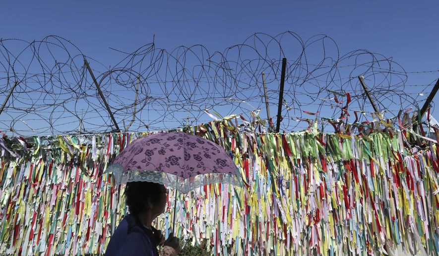 A visitor walks by the wire fence decorated with ribbons carrying messages to wish for the reunification of the two Koreas at the Imjingak Pavilion in Paju, South Korea, Wednesday, Sept. 13, 2017. South Korea said Wednesday it conducted its first live-fire drill for an advanced air-launched cruise missile it says will strengthen its pre-emptive strike capability against North Korea in the event of crisis. (AP Photo/Lee Jin-man)