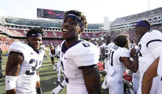 """FILE - In this Sept. 9, 2017, file photo, TCU players Travin Howard (32) and Innis Gaines (6) celebrate their win over Arkansas with teammates after an NCAA college football game in Fayetteville, Ark. Travin Howard and the rest of the TCU defenders don't worry about going from stifling a grind-it-on-the-ground offense one week to facing a big-passing team the next. """"You're just trusting in coach Gary Patterson's way,"""" the Horned Frogs' top tackler said. (AP Photo/Michael Woods, File)"""