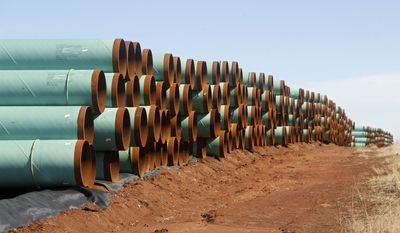 In this Feb. 1, 2012, file photo, miles of pipe ready to become part of the Keystone Pipeline are stacked in a field near Ripley, Okla. (AP Photo/Sue Ogrocki, File)