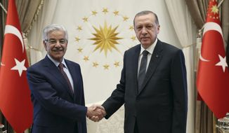 Turkey's President Recep Tayyip Erdogan, right, shakes hands with Pakistan's Foreign Minister Khawaja Muhammad Asif, left, prior to their talks at the Presidential Palace in Ankara, Turkey, Tuesday, Sept. 12, 2017.(Presidency Press Service via AP, Pool)