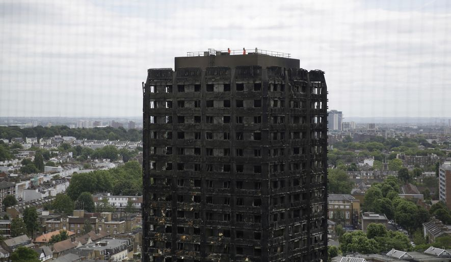 """In this Friday, June 16, 2017, file photo, emergency workers walk on the roof of the fire-gutted Grenfell Tower in London. The head of a government-ordered inquiry into the London tower block fire that killed at least 80 people has acknowledged Thursday, Sept. 14, 2017, that survivors feel a """"great sense of anger and betrayal."""" (AP Photo/Matt Dunham, File)"""